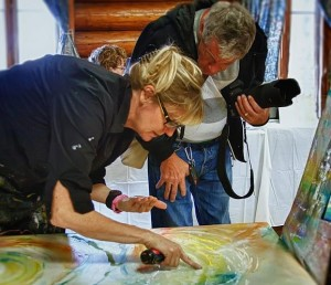 Patty Kingsley inspects a painting